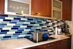 lovely-kitchen-interior-design-for-small-space-with-sectional-kitchen-island-below-mosaic-blue-glass-tile-backsplash-below-mounting-cabinet-and-lucite-glass-cabinet-door